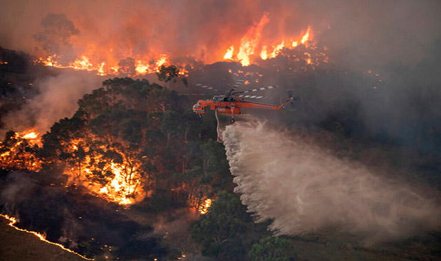 A helicopter tackles a wildfire in East Gippsland on December 30, 2019. Photo: State Government of Victoria.